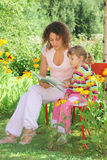 Woman reads book to little girl in garden Stock Photos