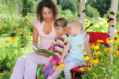 Woman reads book to two little girls in garden Royalty Free Stock Images