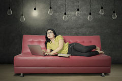 Woman reads book and use laptop under lamp Royalty Free Stock Photos