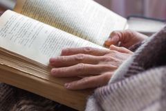 A woman reads a book. A woman holds a book in her hands. Bible r royalty free stock image