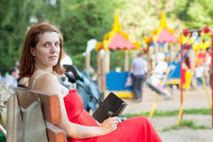 Woman reads e-book against playground area. Pregnancy woman reads e-book against playground area stock photo