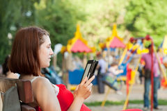 Woman reads e-book against  playground area Royalty Free Stock Images