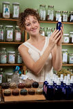 A woman reads the ingredient list on a bottle Royalty Free Stock Photography