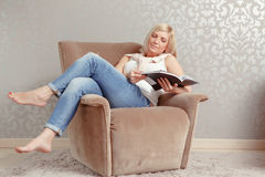 Woman reads a magazine in the armchair Royalty Free Stock Images