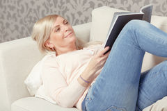 Woman reads magazine in the armchair Stock Image