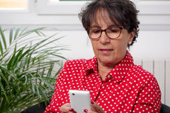 Woman reads a message on her phone Stock Photos