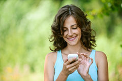 Woman reads message to mobile phone stock images