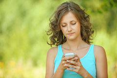 Woman reads message to mobile phone Royalty Free Stock Photos