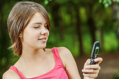 Woman reads message to mobile phone. Charming young woman reads message to mobile phone in park Royalty Free Stock Image