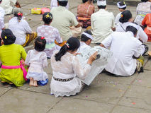 Woman reads newpaper while participating on a religious ceremony royalty free stock image