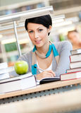 Woman reads at the reading hall. Woman with green apple surrounded with piles of books reads sitting at the table at the library. Learning Stock Photos