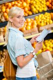 Woman reads shopping list near the heap of fruits Royalty Free Stock Photo