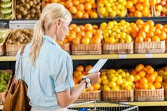 Woman reads shopping list near the pile of fruits Stock Images