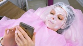 Woman reads something in a mobile phone lying on the procedure in the cosmetoloist`s office with a mask on her face. Woman reads something in a mobile phone stock video footage