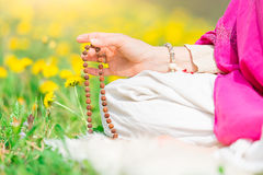 Woman reads the yoga mantra during practice with the mala. On a flowery meadow in spring royalty free stock photography