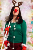 Woman ready for Christmas. Woman wearing festive decorations and holding a mop ready for Christmas with colorful bokeh in the background royalty free stock photo