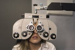 Woman ready for eye test with phoropter and calibrating glasses Stock Images