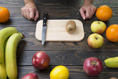 Woman is ready to cut fruit with a knife. Stock Image