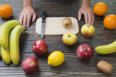 Woman is ready to cut fruit with a knife. Royalty Free Stock Image