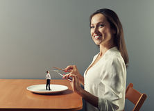 Woman ready to eat small man Stock Images