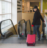 Woman ready to go on a trip with red suitcase in tow Royalty Free Stock Photo