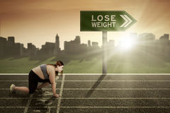 Woman ready to lose weight concept. Young woman wearing sportswear and ready to run on the track with a text of lose weight on the signpost Royalty Free Stock Photos