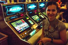 Woman ready to play at slot machines. Las Vegas, NV, USA - 13th July 2013: Smiling young woman ready to play at slot machine in Bellagio Casino Royalty Free Stock Images