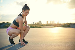 Woman ready to run while squatting near ground Royalty Free Stock Photography
