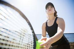 Woman ready to serve the tennis ball. Confident young hispanic female tennis player serving ball outdoors on tennis court Royalty Free Stock Photos