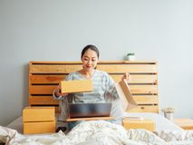 Woman ready to ship the products of her online store to the customer. Concept of work at home online business. Asian woman ready to ship the products of her stock photo