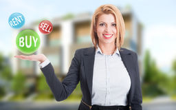 Woman real estate agent holding buy, sell and rent offers. On residential house background Royalty Free Stock Image