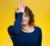 Woman realizes mistake, regrets, slapping hand on head to say duh. Portrait sad middle aged woman realizes mistake, regrets, slapping hand on head to say duh stock image