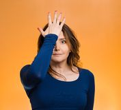 Woman realizes mistake, slapping hand on head to say duh, Royalty Free Stock Image
