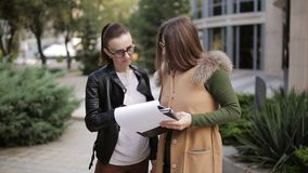 Woman woman realtor and client to discuss the documents on the background of the rental building. Realtor woman offers the woman a great building for rent stock video footage