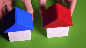 Woman realtor placing toy houses with red and blur roofs against green background. Real estate agency and development. Woman holding toy houses with red roof stock video