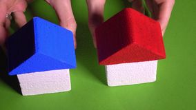 Woman realtor placing toy houses with red and blur roofs against green background. Real estate agency or development Royalty Free Stock Photos