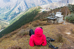 Woman rear view lying above Tengboche village buddhist monastery Stock Photography