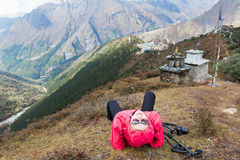 Woman rear view lying above Tengboche village buddhist monastery Stock Photos