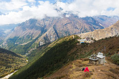 Woman rear view lying above Tengboche village buddhist monastery Royalty Free Stock Images