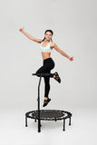 Woman on rebounder jumping up showing thumbs up with smile Royalty Free Stock Images