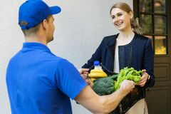 Woman Receive Online Grocery Order Box From Delivery Man At Home Stock Photography