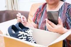 Woman received online shopping parcel opening boxes. And buying fashion items with credit card stock photography