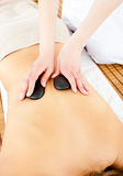 Woman receiving a back massage with hot stones Stock Image
