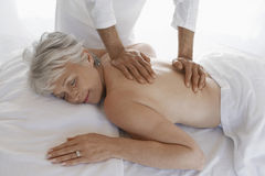 Woman Receiving Back Massage. Side view of a senior woman receiving back massage at spa royalty free stock photography