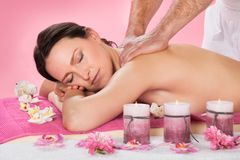 Woman receiving back massaging in spa Royalty Free Stock Image