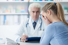 Woman receiving bad news from her doctor. Patient in the doctor's office receiving bad news, she is desperate and crying with head in hands Royalty Free Stock Images