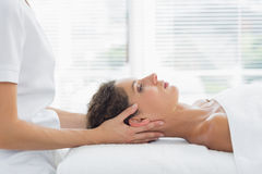Woman receiving body massage in health spa. Side view of woman receiving body massage in health spa Stock Photography