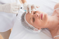 Woman receiving botox injection on her forehead Royalty Free Stock Photo