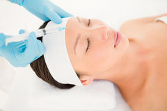 Woman receiving botox injection on her forehead Royalty Free Stock Photos