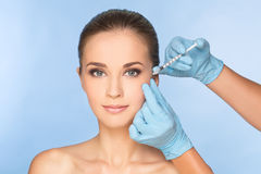 Woman receiving BOTOX injections. Attractive young brunette woman receiving BOTOX injections around eyes from hands in blue latex gloves with blue background royalty free stock photography